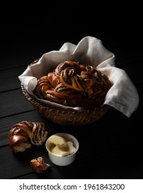 Piece of poppyseed knot and butter beside woven basket of freshly baked buns on wooden table