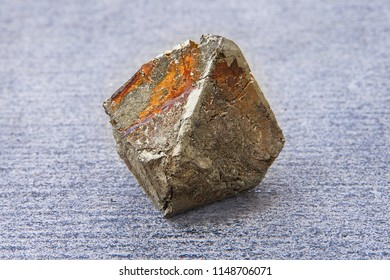 A piece of pyrite crystal with rust spots, lying on a gray stone slab. Close-up of natural rock specimen - rough iron pyrite (fool's gold) stone on grey background