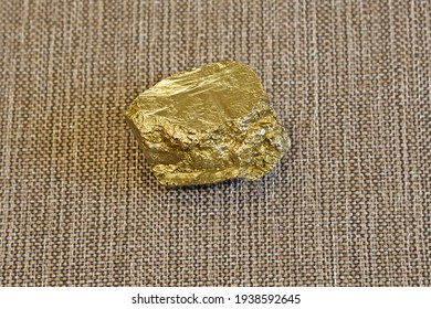 Piece of pyrite on a gray background. For its external resemblance to the noble metal, this mineral has the nickname