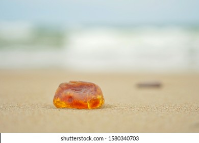 a piece of raw amber thrown onto the shore of the Baltic Sea, closeup photo