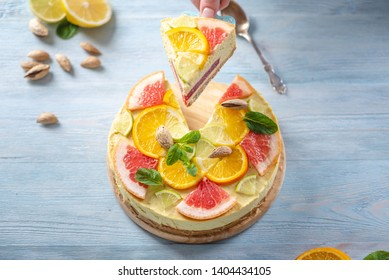 A piece of raw citrus cake with grapefruit, orange, lime and lemon with nuts and mint. Healthy fresh summer dessert. Homemade vegan food