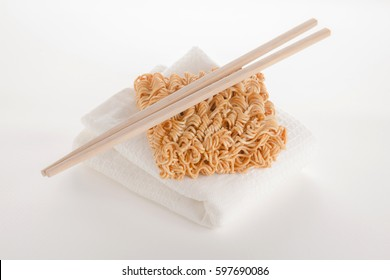 piece of raw instant noodle on white texture cloth with chopsticks on white background