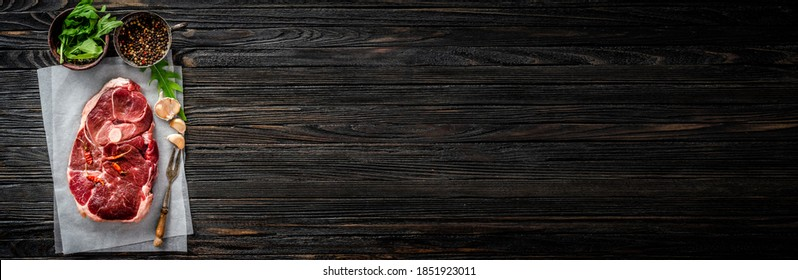 Piece of raw lamb meat on craft paper on dark wooden table, top view with copy space