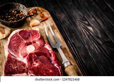 Piece of raw lamb meat with spices on dark wooden table