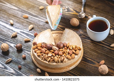 A piece of raw nutty cake decorated with walnut, almond, macadamia and hazelnut on a dark wooden background. Healthy fresh summer vegan dessert. Gluten free and sugar free food