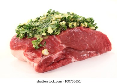 a piece of raw pork roast with a herb paste