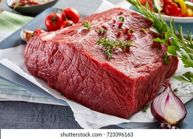 Piece of raw rump steak prepared with spices on plate