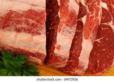 Piece of Raw Scotch Fillet being cut into steaks.