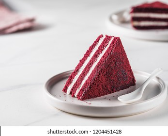 Piece of red velvet cake with perfect texture in matte plate on white marble tabletop. Slice of delicious homemade red velvet cake with raspberry and chocolate. Copy space for text.