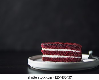 Piece of red velvet cake with perfect texture in matte plate on black tabletop. Slice of delicious homemade red velvet cake with raspberry and chocolate. Copy space for text.