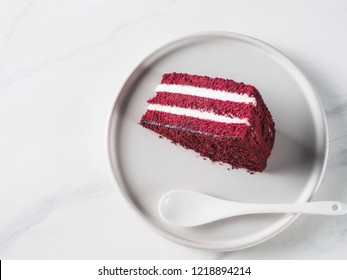 Piece of red velvet cake with perfect texture in matte plate on white marble tabletop. Slice of delicious homemade red velvet cake with raspberry and chocolate.Copy space for text.Top view or flat lay