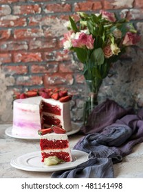 Piece of red velvet cake with strawberries with flowers brick wall background