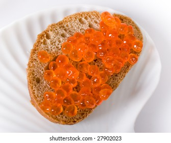 the piece of rye-bread with red cavier on white plate