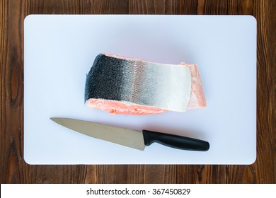 piece of salmon on a white cutting board  and chef's knife on wooden background, top view