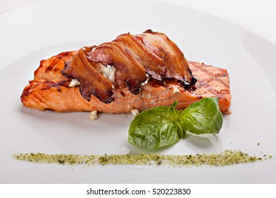 A piece of salmon steak with bacon and cheese.