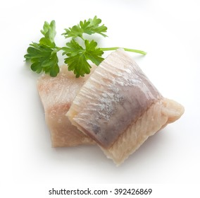 Piece of salted herring with fresh green parsley on the white plate
