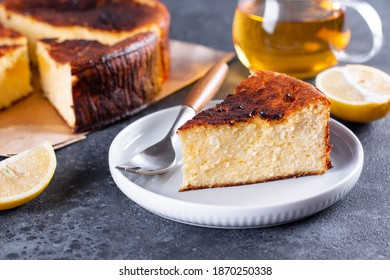 Piece of San Sebastian Basque Cheesecake on the plate on a table with lemon and a cup of tea