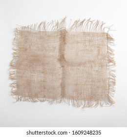 Piece of shabby linen cloth. Sack burlap fabric patch. Coarsely woven rough fabric with fringed edges. Eco friendly hessian material. Textile rectangular shred on white background. Sustainable living