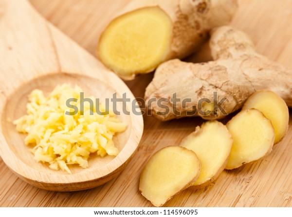 Piece slice and crushed of ginger against a wood worktop