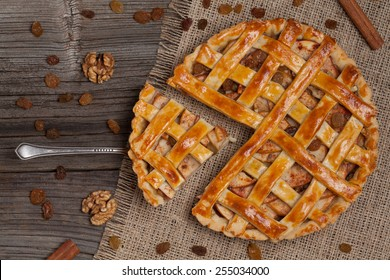 A piece of sliced apple pie with nuts and cinnamon on metal spatula on vintage wooden background texture. Top view