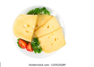 Piece and slices of cheese in a plate with herbs and tomatoes isolated on white background. top view
