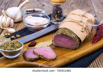 Piece of smoked Ham with garlic and spice on wooden background. Rustic style. Studio Photo