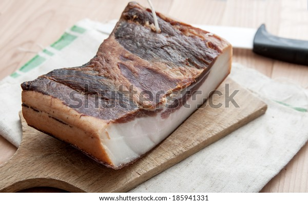 Piece of smoked pork bacon  on wooden board