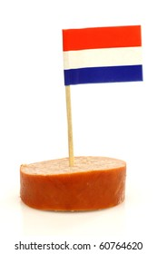 a piece of smoked sausage with a Dutch flag toothpick on a white background