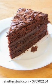 A piece of soft chocolate cake on white plate.