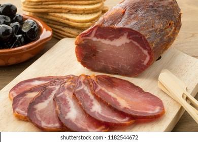 Piece of spanish Lomo Embuchado meat and slices