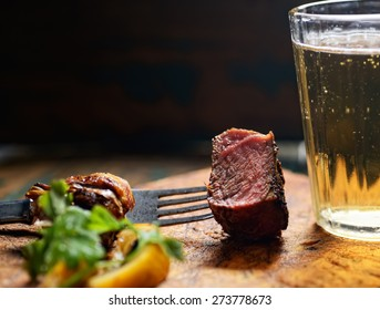 piece of steak on a fork with a beer