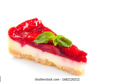 A piece of strawberry cake and a mint leaf, isolated on white