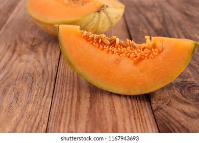 Piece of sugar cantaloupe melon on wooden surface