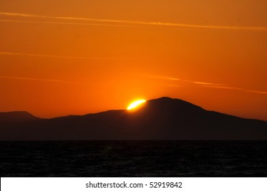 Piece of sun behind the mountains at sunset