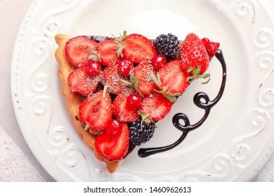 Piece of tasty chocolate strawberry cake on plate, closeup