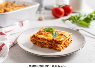 Piece of tasty hot lasagna served with a basil leaf on a gray plate. Italian cuisine, menu, recipe. Homemade meat lasagna. Close up, side view