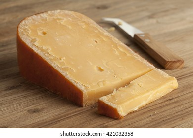 Piece of three year old Gouda cheese on a cheeseboard