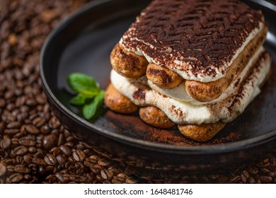 Piece of Tiramisu on a black plate with some Coffeebeans