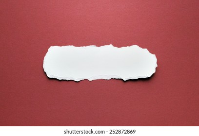 A piece of torn paper on a red background. Space for text.