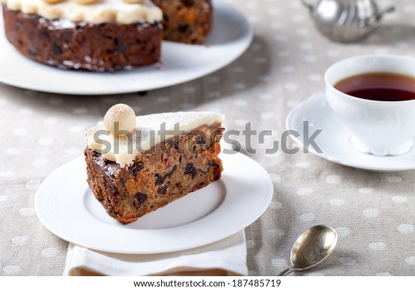 Piece of Traditional English Easter cake with marzipan decoration on a white plate