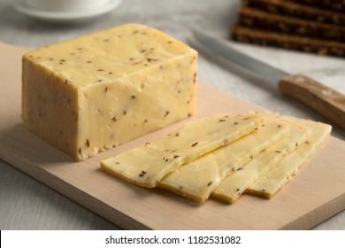 Piece of traditional German caraway cheese and slices