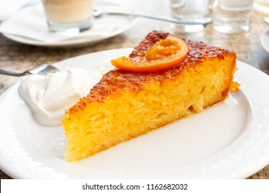 A piece of traditional greek orange cake with sour cream on white plate.