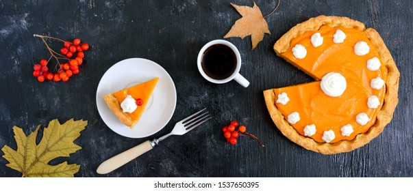 Piece of traditional homemade pumpkin pie and a cup of coffee on a black background. Healthy food, dessert for gourmets. Thanksgiving theme. Traditional autumn baking. Top view.