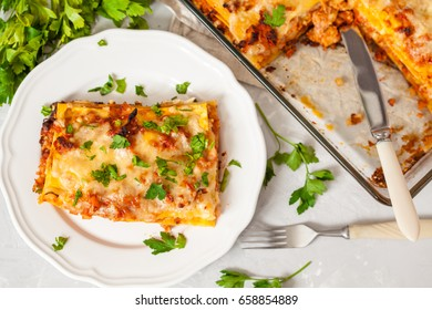 Piece of traditional Italian meat lasagna on a white plate.