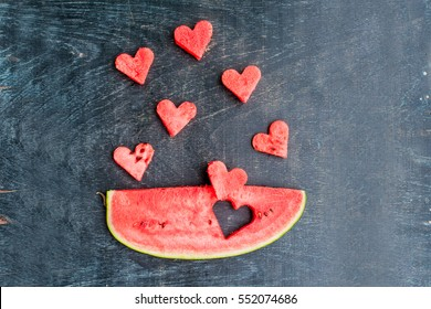 Piece of watermelon and hearts on the old wooden background. Space for text. Flat lay composition. love concept. Valentine's Day Concept