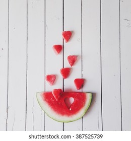 Piece of watermelon and hearts at white background. Flat lay