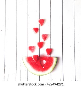 Piece of watermelon and hearts at white background, flat lay composition