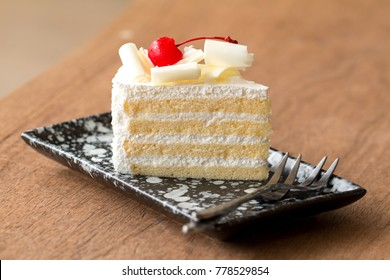 Piece of white cake with vanilla frosting and cherry jelly, topped with white cheese.