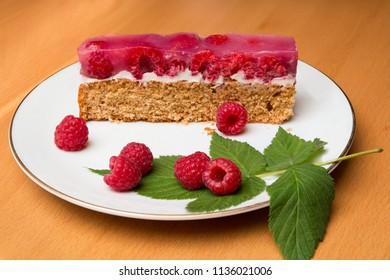 piece of wholemeal raspberry cake on a porcelain plate and wooden table, decorated with a green raspberry leaf