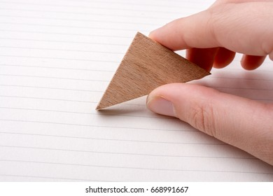 Piece of wood in the shape of a triangle on paper